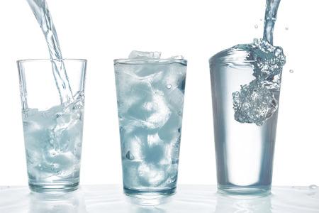 tomando agua: El agua potable se vierte en vidrio con cubitos de hielo Foto de archivo