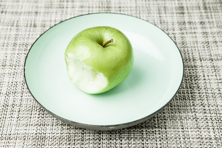 missing bite: Green apple on plate, missing bite