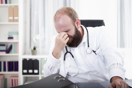 overstress: Over worked doctor sitting at desk