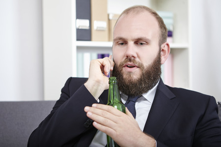 Businessman talking on phone holding beer bottle photo