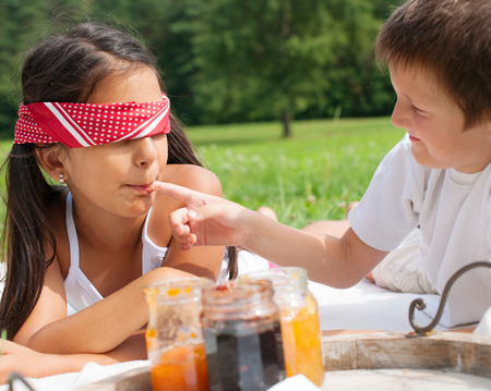 Brother and sister blind tasting different jams Stock Photo