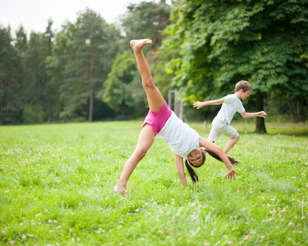 rampage: Brother and sister cartwheeling in meadow Stock Photo