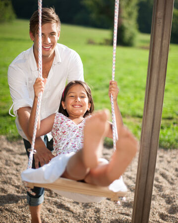 barefoot man: Father swinging daughter at playground
