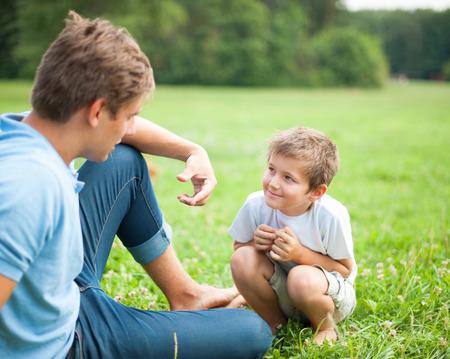padres hablando con hijos: Padre e hijo que hablan en el parque Foto de archivo