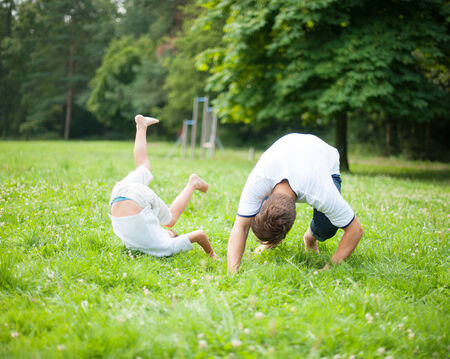 somersault: Father and son somersaulting on the ground