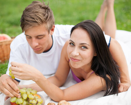 Happy young couple having grapes at picnic photo