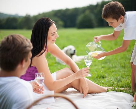 alimentos y bebidas: Familia de joven en la comida campestre en el parque, muchacho servir agua