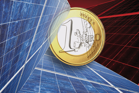 One euro coin and solar panel against red background, close up. photo