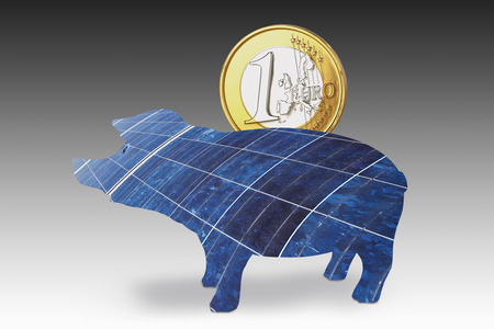 Solar panel piggy bank with one euro coin against gray background. photo