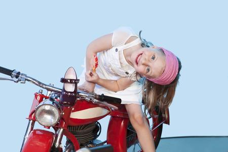 hairband: Germany, Landshut , little girl (4-5) riding carousel bike, smiling Stock Photo