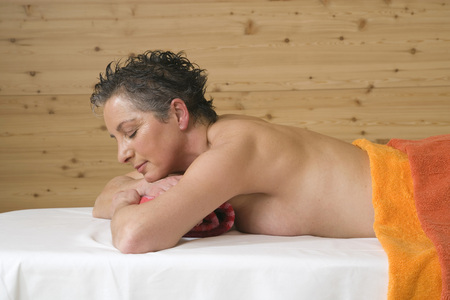 Mature woman relaxing on massage table, eyes closed, portrait