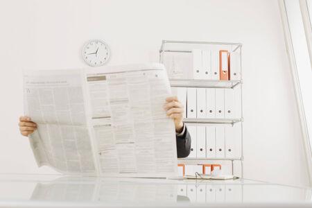 everyday jobs: Businessman reading a newspaper, portrait