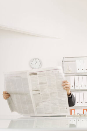 everyday jobs: Businessman reading newspaper, portrait