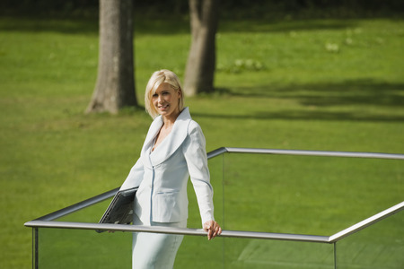 anticipate: Germany, businesswoman with laptop standing on external staircase