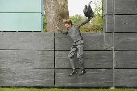 only one mid adult man: Germany, businessman jumping from wall