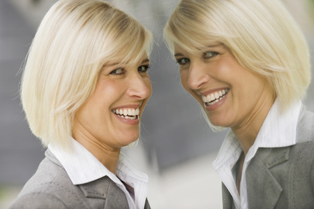 mirror image: Germany, businesswoman looking at mirror image Stock Photo