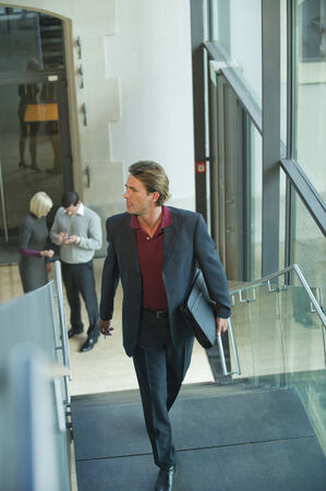 collegue: Gedrmany, businessman climbing stairs, people in background