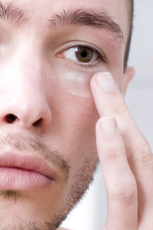 self conceit: Man applying face cream, close-up