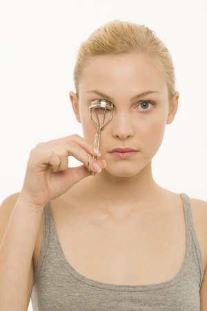 Young woman using eyelash curler, portrait photo