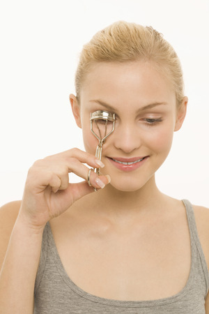 Young woman using eyelash curler, smiling, portrait photo