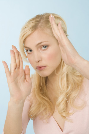 solicitude: Blonde woman defending herself, portrait Stock Photo