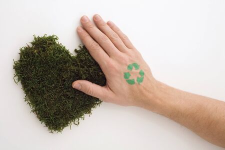unrecognisable people: Hand with green sign on heart-shaped grass