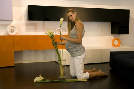 glass vase: Pregnant woman arranging flowers in glass vase