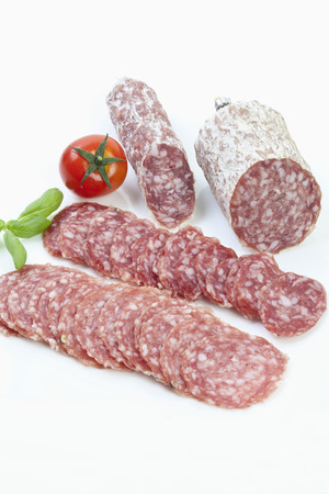 salami slices: Salami slices and tomato on white background Stock Photo