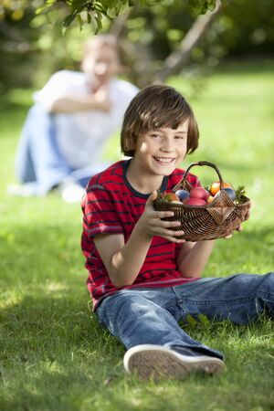 Germany, Boy holding Easter eggs with father in background photo