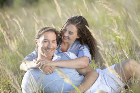 Germany, Bavaria, Man and woman embracing in meadow, smiling photo