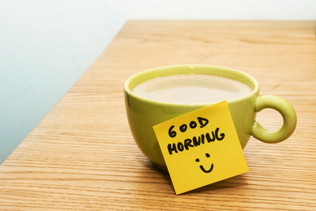 Cup of coffee, sticky note good morning and smiley