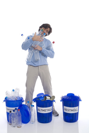 discarded metal: Man holding plastic bottles, standing by dust bins Stock Photo