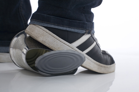 tin can: Man stepping on tin can Stock Photo