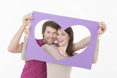 looking through frame: Couple looking through heart shaped frame