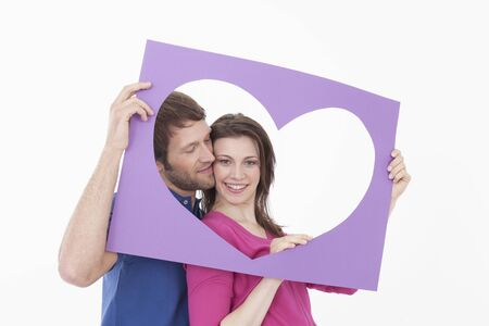 looking through frame: Woman looking through heart shaped frame with man eyes closed Stock Photo