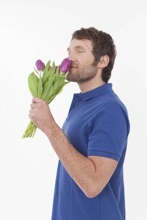sensory perception: adult man smelling flowers, smiling Stock Photo
