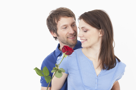 gifting: Man giving red rose to woman, smiling Stock Photo