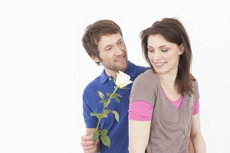 gifting: Man giving rose to woman, smiling Stock Photo