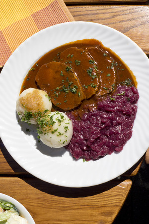 Sauerbraten with red cabbage and potatoe dumplings on plate