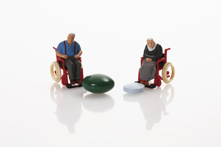 male likeness: Pensioners figurine and pills on white background Stock Photo