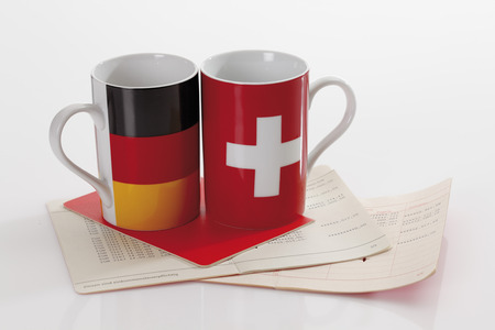 german swiss: Swiss and german flag cups with bank book on white background Stock Photo