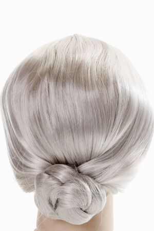 female likeness: Female mannequin head wearing grey wig against white background