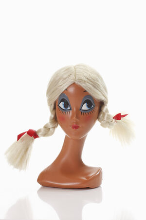 female likeness: Female mannequin head wearing blonde wig with plaits