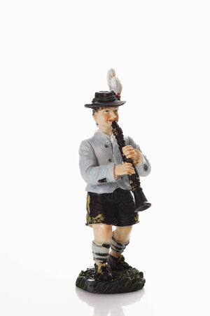male likeness: Bavarian figurine playing clarinet on white background