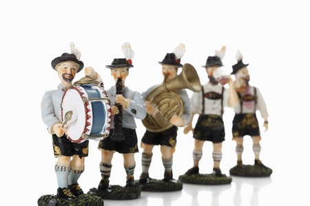 male likeness: Bavarian figurines playing music on white background