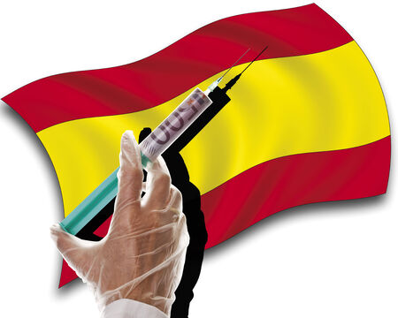 spanish flag: Close up of human hand with cash injection on spanish flag Stock Photo