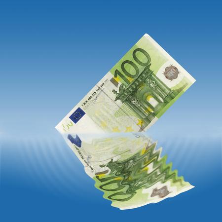 western script: 100 euro note sinking in water Stock Photo