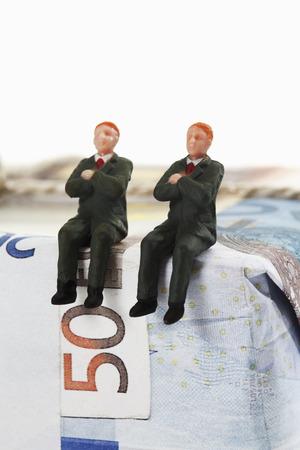 male likeness: Gerentes estatuillas que se sientan en el paquete de billetes de euro Foto de archivo