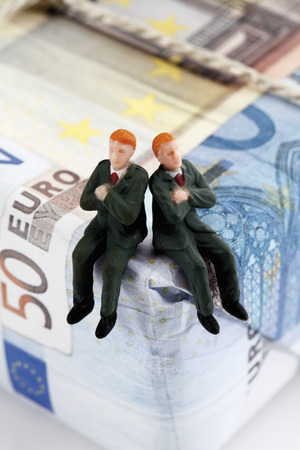western script: Managers figurines sitting on package of euro notes Stock Photo