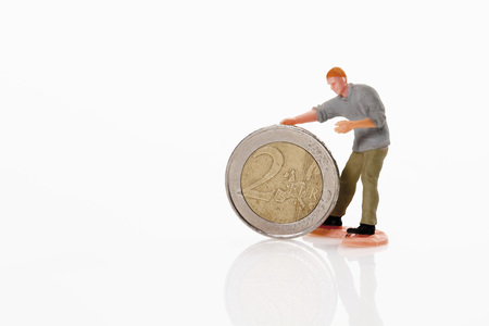 male likeness: Worker figurine rolling 2 euro coin